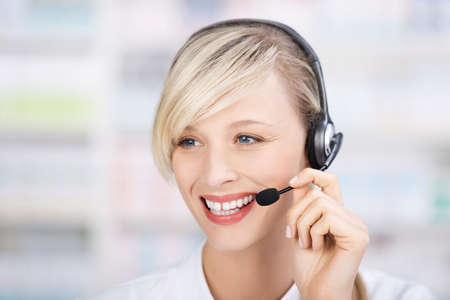 Portrait of a friendly female pharmacist talking at the phone using headsets and holding the microphone photo