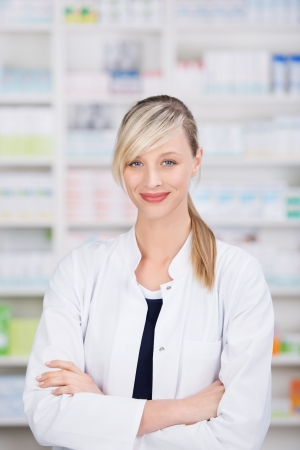 Portrait of a friendly female pharmacist with crossed arms with the medicine shelves in the background Stock Photo - 21156980