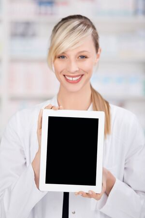 Smiling female pharmacist holding a digital tablet with an empty black display for copy-space photo