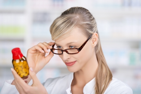 Female pharmacist attentively reading the medicine label of a bottle of pills