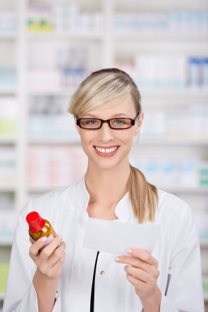 checking ingredients: Female pharmacist smiling at camera holds a medicine prescription and a bottle of pills