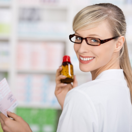 checking ingredients: Friendly pharmacist with medicine prescription and bottle of pills smiling at camera Stock Photo