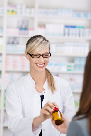Friendly and smiling female pharmacist gives a bottle of pills to a patient photo