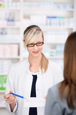 Female pharmacist talks to patient about the medical prescription inside the pharmacy photo