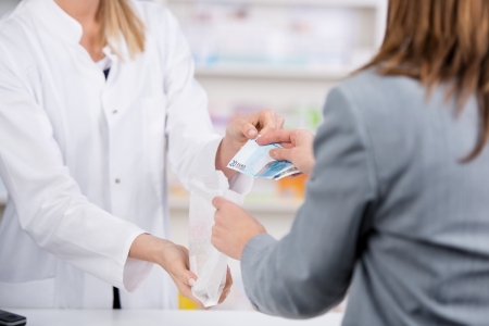 doctor holding money: Patient pays for the medicine to the pharmacist with a twenty euro note while receiving the bag Stock Photo