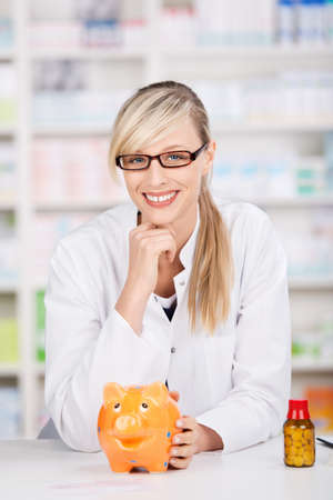 Smiling friendly female pharmacist poses with a piggy-bank and a bottle by her side. Concept for saving in healthcare treatments photo