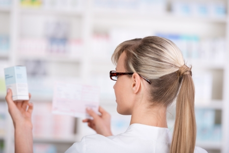 Female pharmacist picks up medicine form the shelf while confirming with the prescription photo