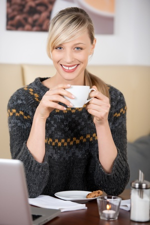 Beautiful blond woman drinking a cup of coffee in the coffee shop smiling at camera Stock Photo - 21164412