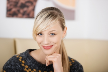 Portrait of a smiling beautiful and seductive blond woman holding the chin with the hand and wearing a knitwear sweater Stock Photo - 21164422