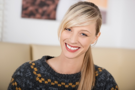 chilling out: Portrait of a smiling beautiful and seductive blond woman leaning her head and wearing a knitwear sweater