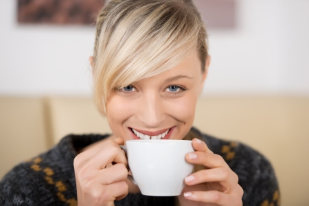 Attractive blond woman smiling behind a cup of coffee in a coffee shop photo