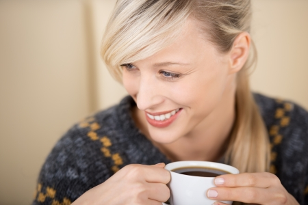 Attractive smiling blond woman enjoying her cup of coffee in a coffee shop Stock Photo - 21164407