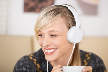 coffeeshop: Beautiful blond woman smiling while listening to music on large white headphones music and drink a cup of coffee
