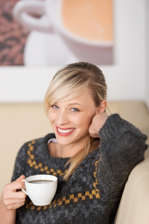 Smiling woman enjoying coffee in a cafe sitting relaxing with a cup of espresso in her hand Stock Photo - 21164413