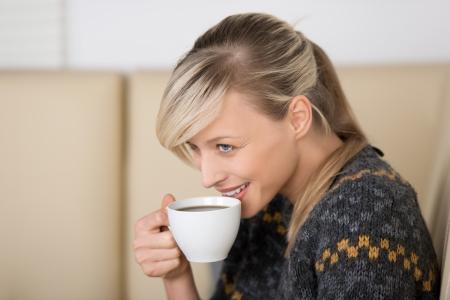 Glimlachende vrouw met een vers gezet kopje espresso koffie in haar hand, zittend op een comfortabele bank, met kop en schouders zijaanzichtportret