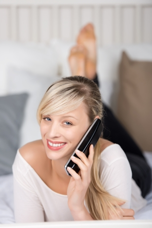 Smiling female calling through telephone in the bedroom Stock Photo - 21164429