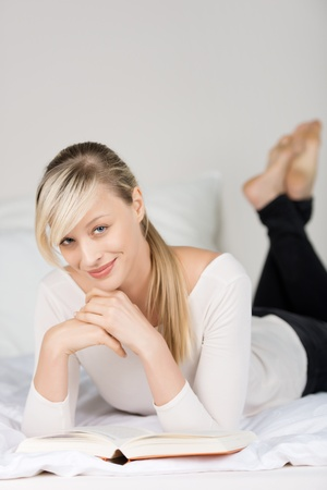 woman reading book: Close up portrait of relaxing woman reading book in her bedroom Stock Photo
