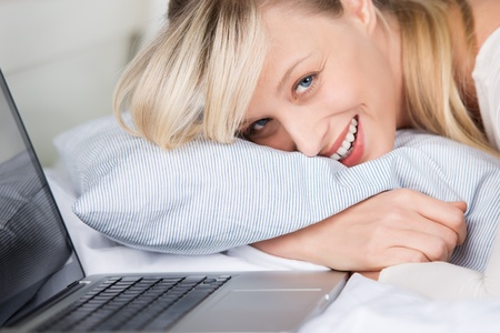 Smiling young female lying with laptop at her bedroom Stock Photo - 21164433
