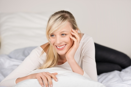 Happy fresh female looking at something while lying on her bed Stock Photo - 21164438