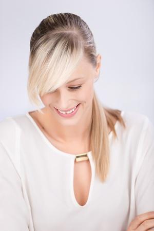 cola mujer: Sonriente mujer rubia mirando hacia abajo sobre el fondo blanco