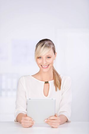 fair skin: Smiling blond woman holding digital tablet on the table Stock Photo