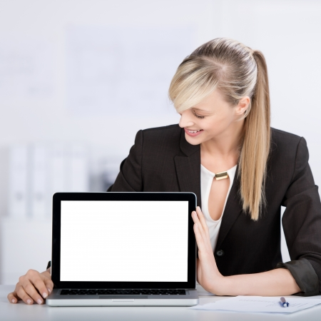 Smiling blond woman shows the laptop in a front view shot photo