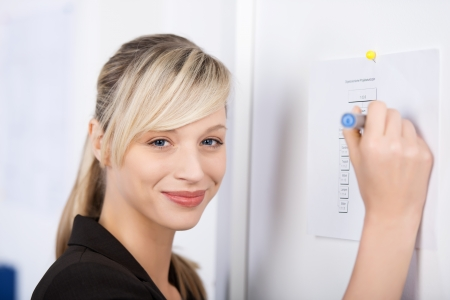 Smiling businesswoman writes something on the wall photo