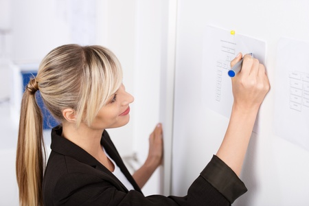 Young blond businesswoman writes something on the chart photo