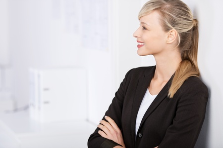 Businesswoman posing with arms crossed and leaning on the wall photo