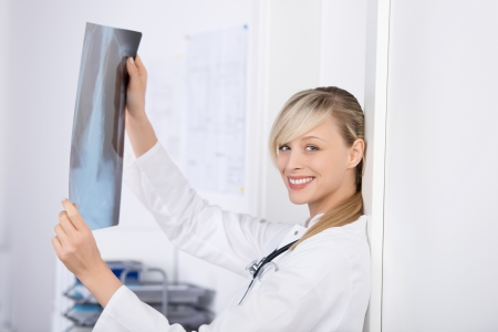 Attractive blond doctor holding x-ray image in the lab photo