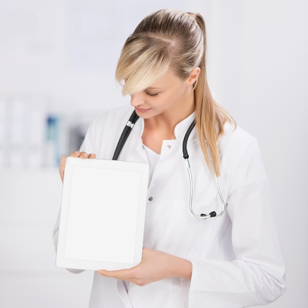Pretty young doctor with stethoscope shows the digital tablet photo