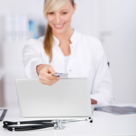 assistent: Smiling doctor giving insurance card to someone