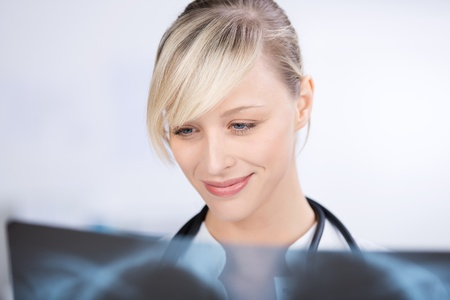 Smiling blond doctor checking the x-ray image Stock Photo - 21164819