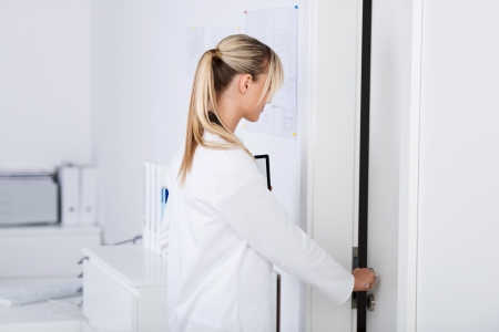 Beautiful young doctor opening the door in the lab photo