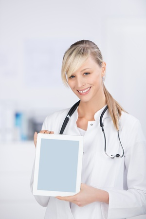 Smiling blond doctor with stethoscope shows the digital tablet photo
