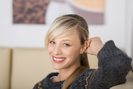 Seductive blond woman with a friendly smile sitting on a coffee shop Stock Photo - 21164823