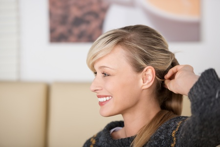 Seductive smiling beautiful blond woman playing with her hair while relaxing in the coffee shop Stock Photo - 21164824