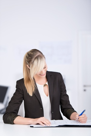 left handed: Smiling businesswoman writing on her book in the office