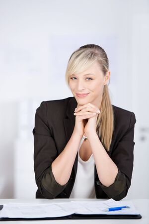 Cheerful businesswoman leaning her chin with hands photo