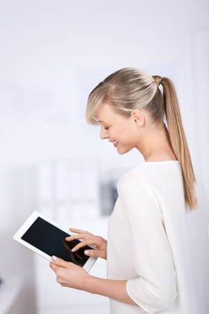 near side: Blond businesswoman reading something with digital tablet Stock Photo