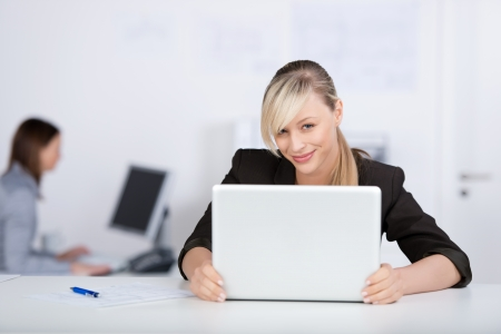 Smiling businesswoman working using laptop on her table photo