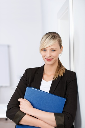 Smiling blond businesswoman holding a blue file while leaning on the wall photo