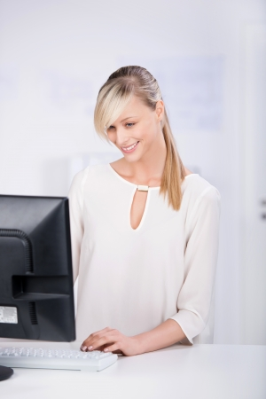 Smiling businesswoman working in front of computer isolated on photo
