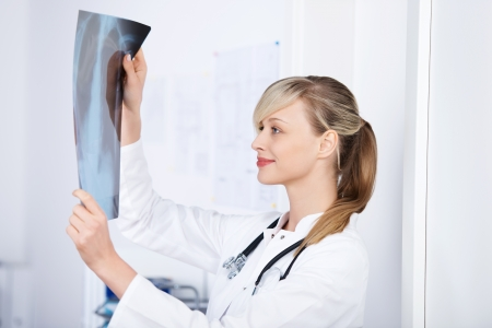 diagnosing: Cheerful blond doctor checking the x-ray image Stock Photo