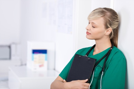 Portrait of doctor leaning on the wall with closed eyes photo