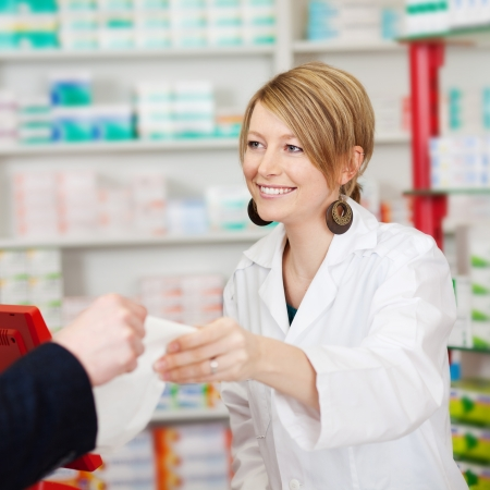 costumer: confident pharmacist passing paper bag to costumer Stock Photo