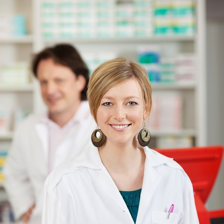 Portrait of happy female pharmacist with coworker in background at pharmacy photo