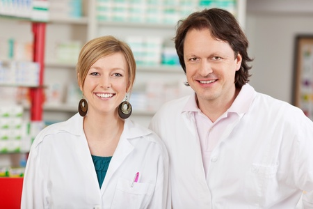 Portrait of happy male and female pharmacists in pharmacy photo