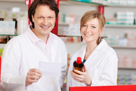 two confident pharmacists in the pharmacy with medicine photo