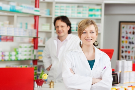 female pharmacist with crossed arms and co worker photo